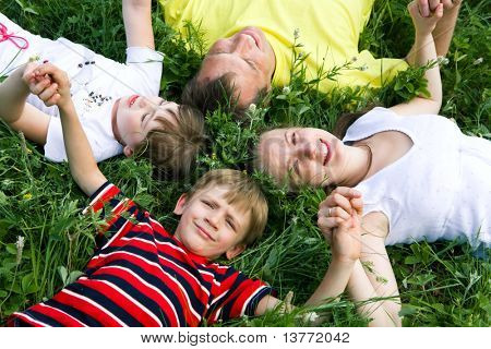 Portrait of family lying on the grass and holding their hands