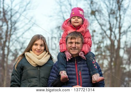Father Mother Little Baby Daughter Together on Weekend Walk on Autumnal Colors Forest Sunny Day Smiling Faces Child Sitting on Daddy Shoulders