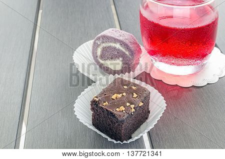 homemade chocolate brownies or chocolate cakes with nuts and cake roll on white paper cup on wooden table.