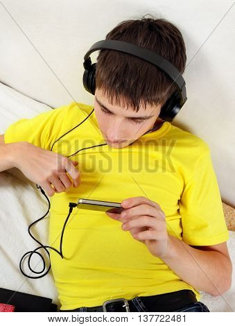 Teenager with Mobile Phone listen to the Music