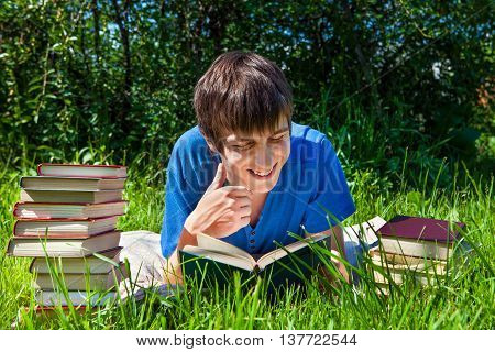 Cheerful Young Man read a Books on the Grass