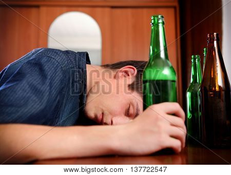 Tired Young Man with Bottle of the Beer at the Home