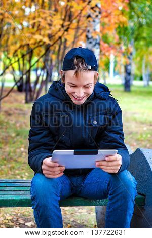 Cheerful Teenager with Tablet Computer in the Autumn Park