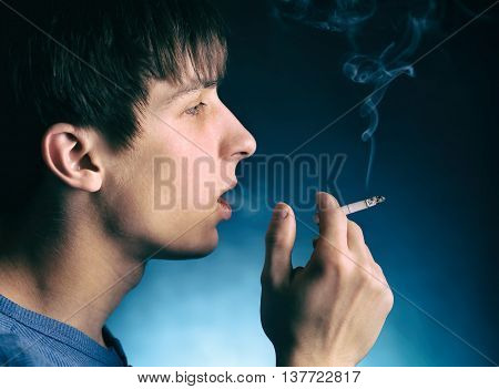 Young Man with Cigarette in the Dark Room