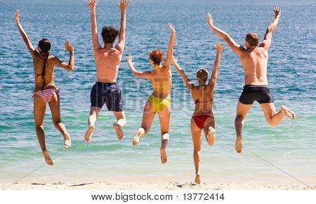 Portrait of five teens jumping in the lake simultaneously