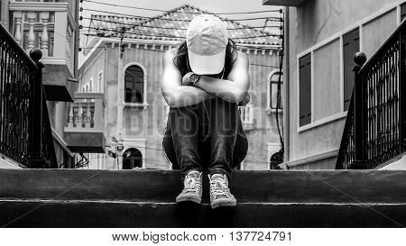 sad woman wearing a hat and hugging knees on stair backand white