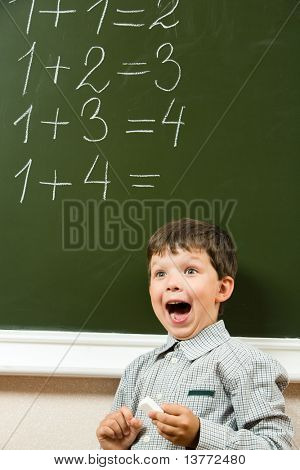 Portrait of happy boy screaming before blackboard with sums on it during lesson