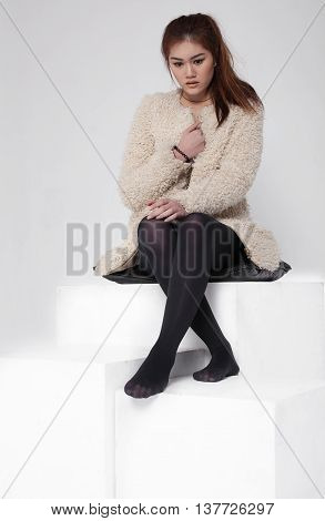 Young asian attractive sexy fashion model with natural hair, beautiful eyes, perfect skin is posing in studio for glamour vogue test photo shoot