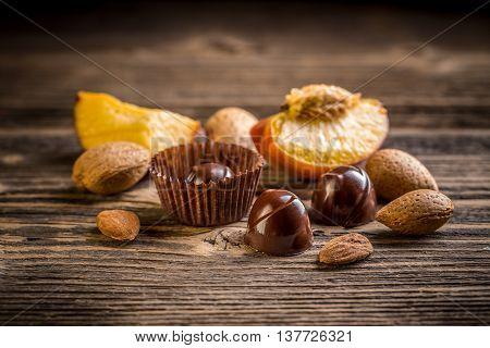 Fine chocolate bonbon on wooden background, studio shot