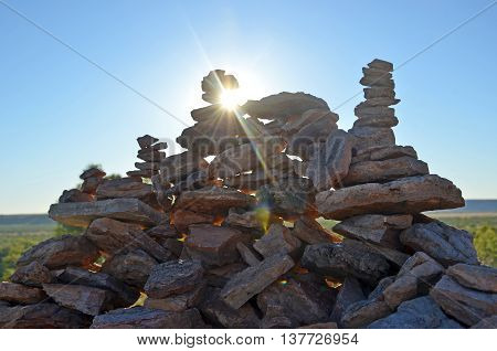Sun flare behind rock cairns in outback Queensland, Australia