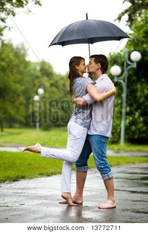 Photo of romantic barefooted couple standing on the road in rain and going to kiss each other