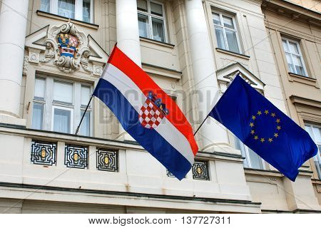Flags of Croatia and European Union against the facade of Croatian Government building in historic Zagreb