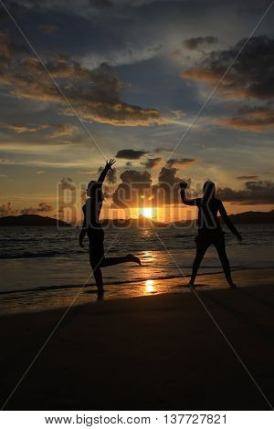 two people are dancing on the sand of the beach at the sunset