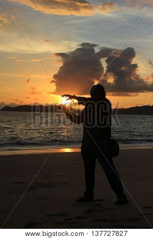 a person silhouette as if grasping the sun at the sunset