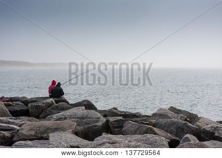 People catch fish from the Baltic Sea breakwater.