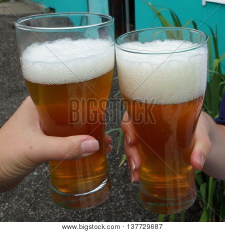 Two glasses of frothy beer in hand