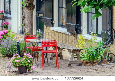 Simple bright red chairs with a small table and an old wooden bench draw attention of passers in a historic Dutch village with many historic buildings.