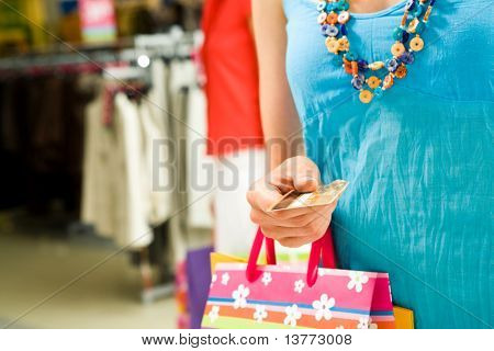 Image of personal credit card in female hand with shopping bags