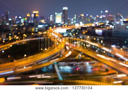 Blurred bokeh lights highway intersection and city downtown background, night view