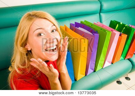 Portrait of woman being happy out of presents placed on sofa