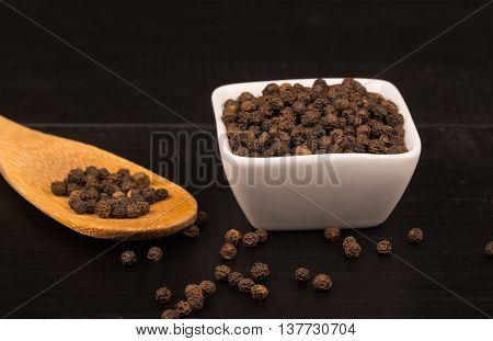 milled black pepper Black pepper corns and Black pepper Powder. White saucers