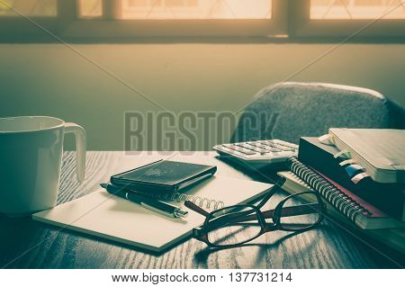 Smartphone put down on table beside notebooks and pen in morning time on work day. Business working at home concept with vintage filter effect