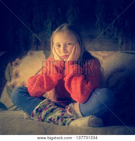 Lone teenager in warm clothing sitting on a sofa.
