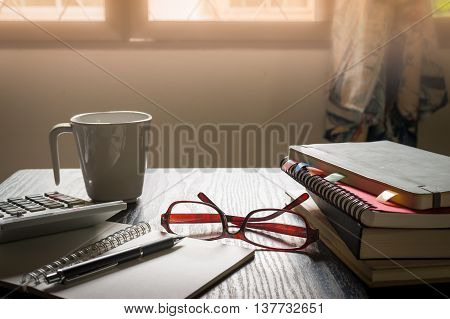 Glasses put down on table beside notebooks and pen in morning time on work day. Freelance business working concept