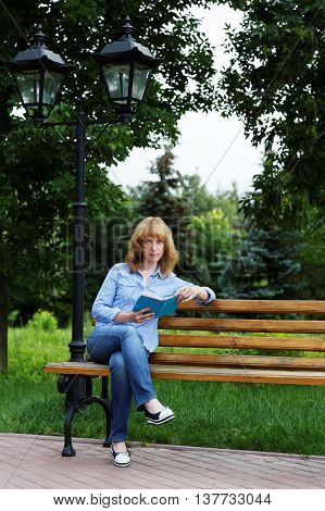 Young Woman On A Bench Reading A Book