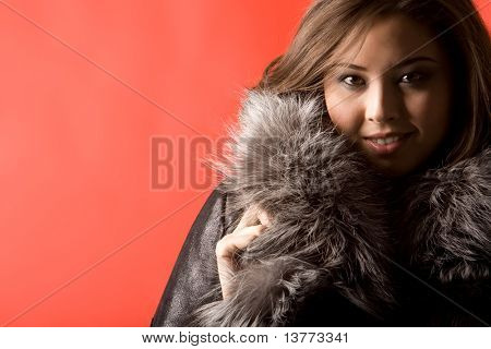 Portrait of beautiful Asian girl wearing fashionable fur coat and looking at camera