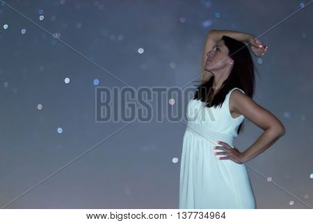 Woman in white long dress under starry night. Woman looking to starry night. Woman under night sky, Blurred night sky. Selective focus shallow depth of field