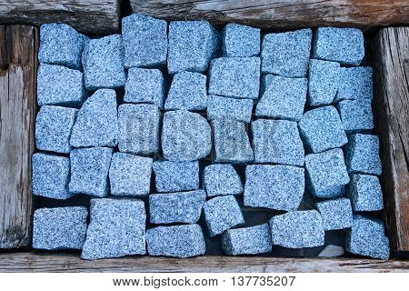 stones granit in a wooden frame texture photo