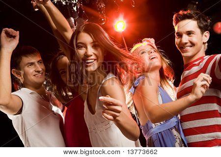 Hermosa chica haciendo gesto significa para unirse a sus amigos bailando en la fiesta