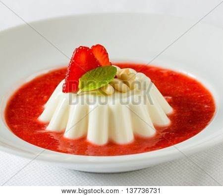 Italian panna cotta dessert with strawberry syrup and pine seeds