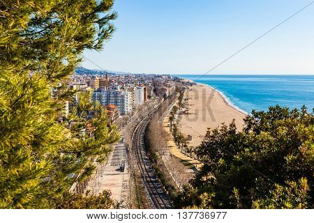 CALELLA, BARCELONA, SPAIN - FEB 19, 2016. View over the touristic town and beach of Calella, Costa Brava, on the Mediterranean coast. The beach of Calella is more than 2 km long.