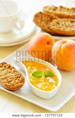 A breakfast table with apricot jam ripe apricots toast and a coffee cup.