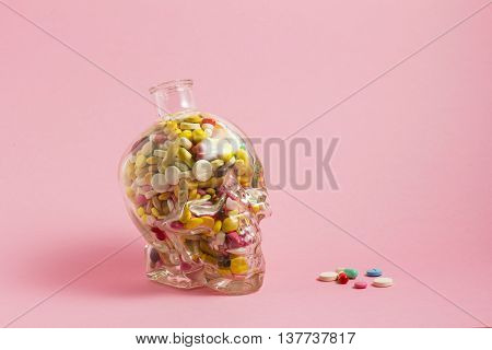 Creative medicine and health care concept photo of a skull glass filled with drugs and pills on pink background.