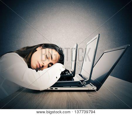 Businesswoman asleep on top of three laptops