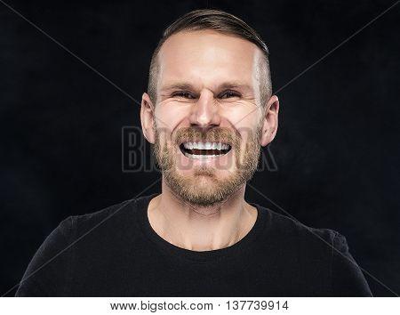 Man in black celebrate success on dark background.