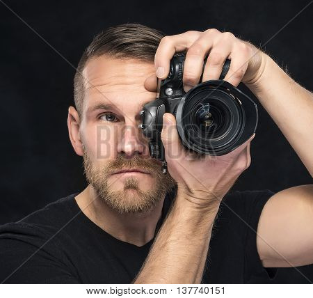 Photographer man with camera on darck background.