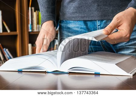 The Man Opening And Browsing The Book Pages