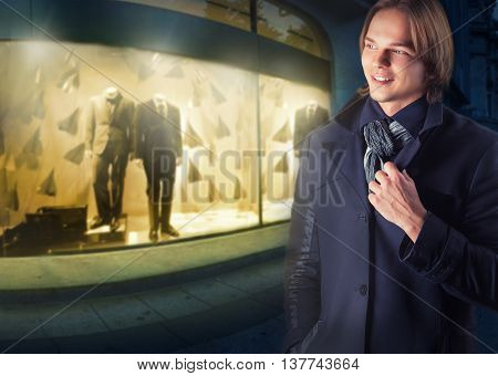 Young handsome man on a background of night shop windows
