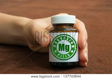 Human Hand Holding A Bottle Of Pills With Magnesium