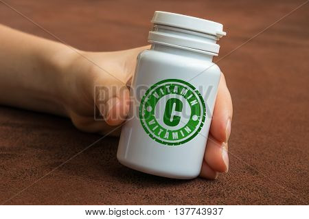 Human Hand Holding A Bottle Of Pills With Vitamin C