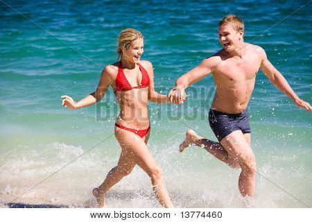 Image of happy teenage couple running by the seashore on summer day