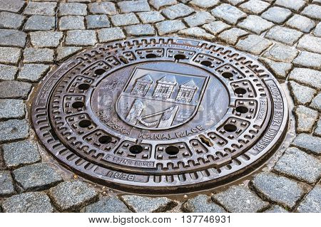 Metal Hatch Sewer Manhole And Cobblestone Pavement