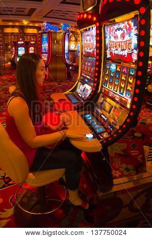 LAS VEGAS - MAY 06, 2016: Concentrated girl playing slot machines in the Excalibur Hotel and Casino