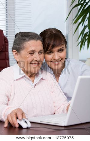 Portrait of young girl with smiling grandmother consulting her how to work with laptop
