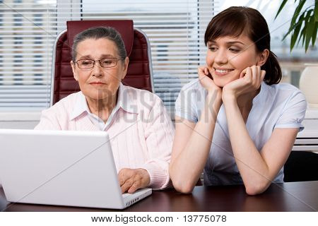 Portrait of young girl smiling while sitting next to her grandmother working with laptop