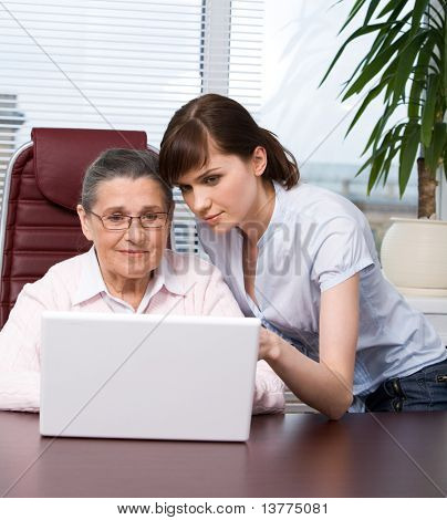 Portrait of young girl explaining her grandmother something while working with laptop